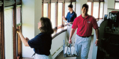 three people cleaning blinds