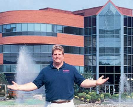 owner standing in front of a brick building